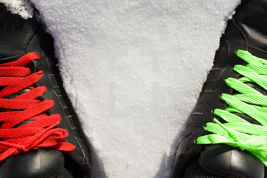 red and green shoe laces on black sneakers standing in snow