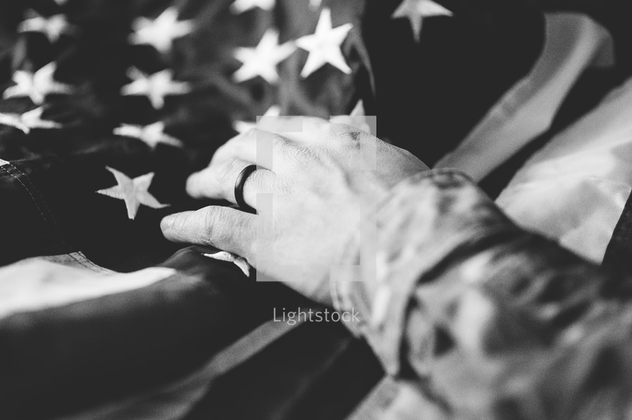 serviceman with hand on an American flag