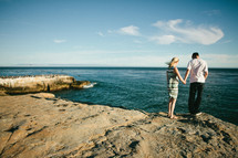 couple holding hands standing on a rocky shore