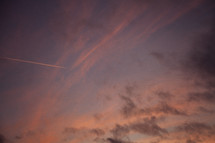 plane contrails in the sky at sunset