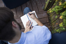 a man writing in a journal outdoors