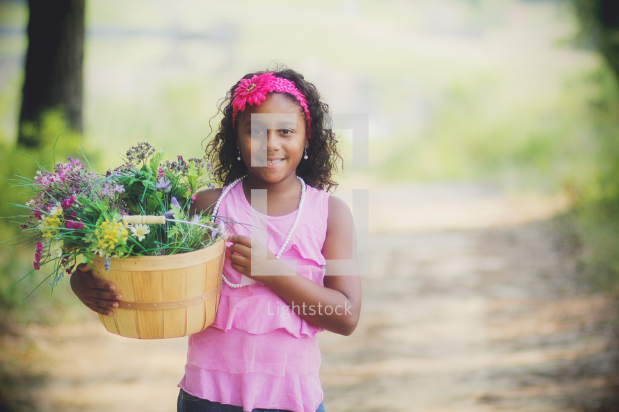 a girl carrying a basket of flowers down a dirt road
