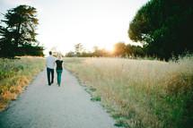 man and woman walking down a gravel road