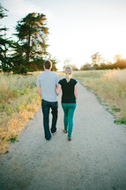 couple walking down a gravel road holding hands