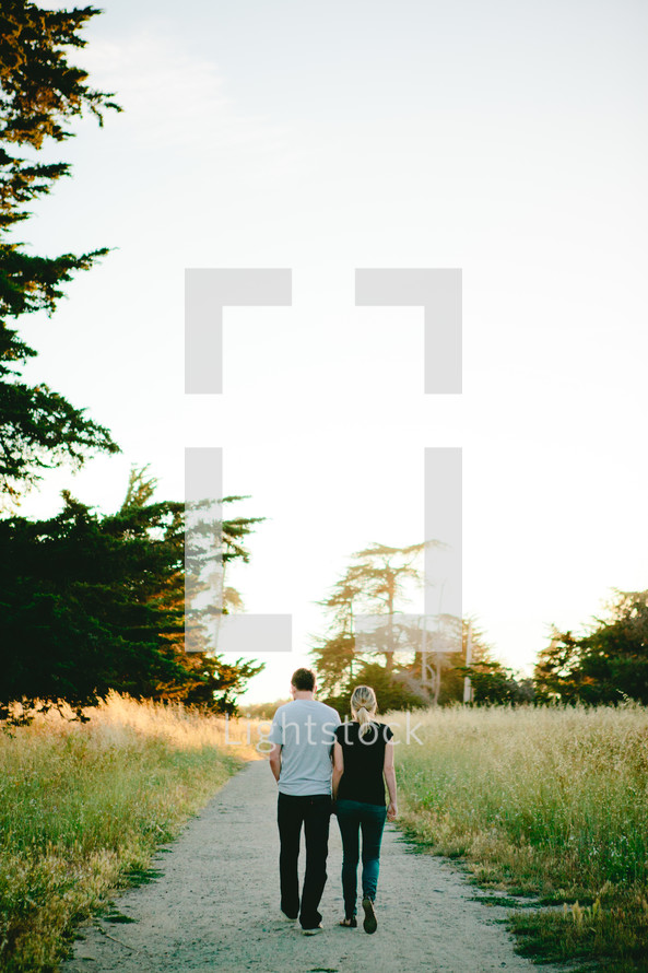 couple walking down a gravel road