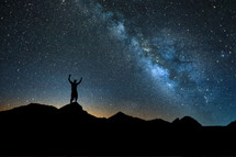 silhouette of a man with raised arms standing under stars in the night sky