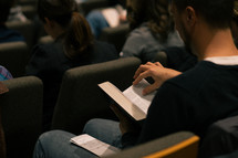 man turning the pages of a Bible at a worship service