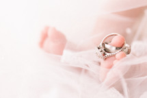 wedding rings on the toes of a newborn