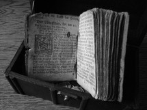 Ancient prayer book from Martin Luther, in a treasure chest on a wood floor.