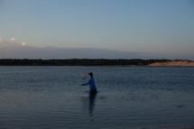 fisherman wading in water