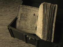 Ancient prayer book from Martin Luther in a treasure chest on a wood floor.