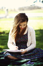 woman writing in a journal outdoors