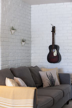 guitar on a wall and couch