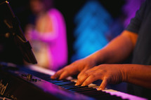 man playing keys on a keyboard