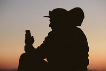 silhouette of a man with a backpack looking at his cellphone at sunset