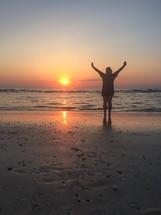 silhouette of a man with raised arms on a beach at sunset