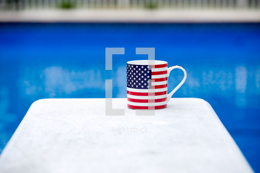 A flag coffee mug on a white table next to a blue swimming pool.