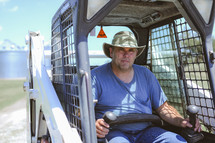 man in a hat in a bob cat tractor