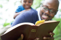 Father and young son reading the Bible.
