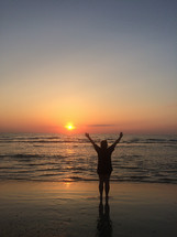 silhouette of a man with raised hands on a beach at sunset