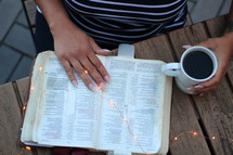 a woman reading a Bible with fairy lights
