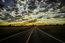 A country Paved Road leading into the Horizon as sun rays beam out of the clouds at sunrise or sunset