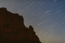 streaks of stars in the night sky and red rock peaks