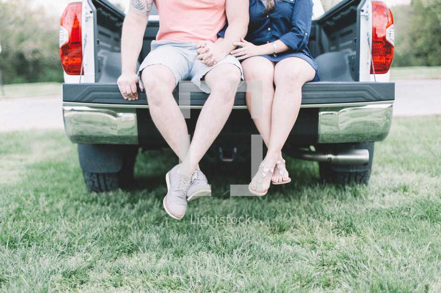 legs of a couple sitting in the back of a pickup truck