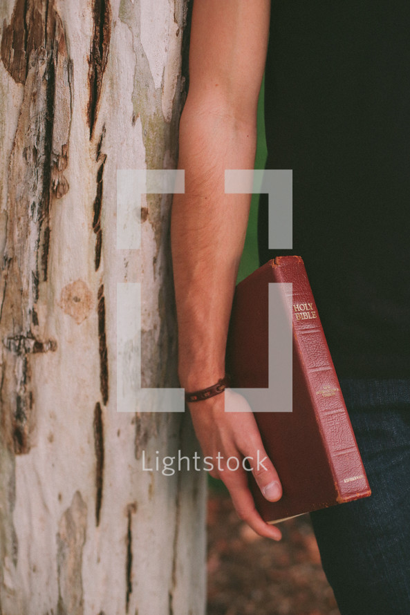 man leaning against a tree holding Bible