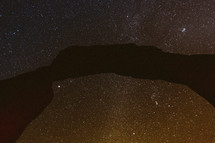 stone arch against stars in the night sky