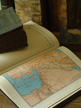 Old books and an old Bible with a map of Israel.