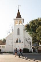 a couple running towards a church