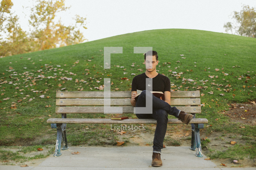 man reading a Bible sitting on a park bench