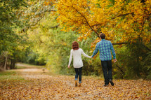 couple walking holding hands through fall leaves