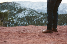 legs of a man standing on red dirt