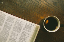 an open Bible and coffee mug on a table