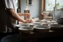 potter making bowls