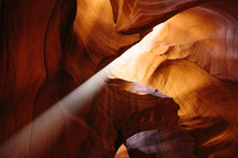 rays of sunlight shining into a red rock cave