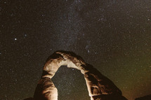stone arch against stars in a night sky
