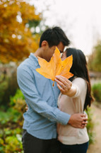 man and woman kissing behind a leaf