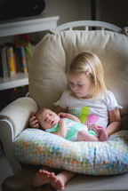 a big sister sitting with her baby brother