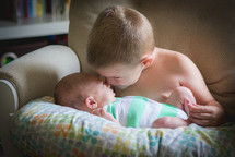 a boy kissing his baby brother