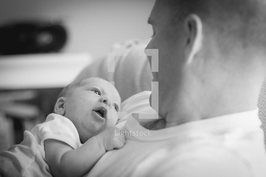 a father rocking her newborn baby