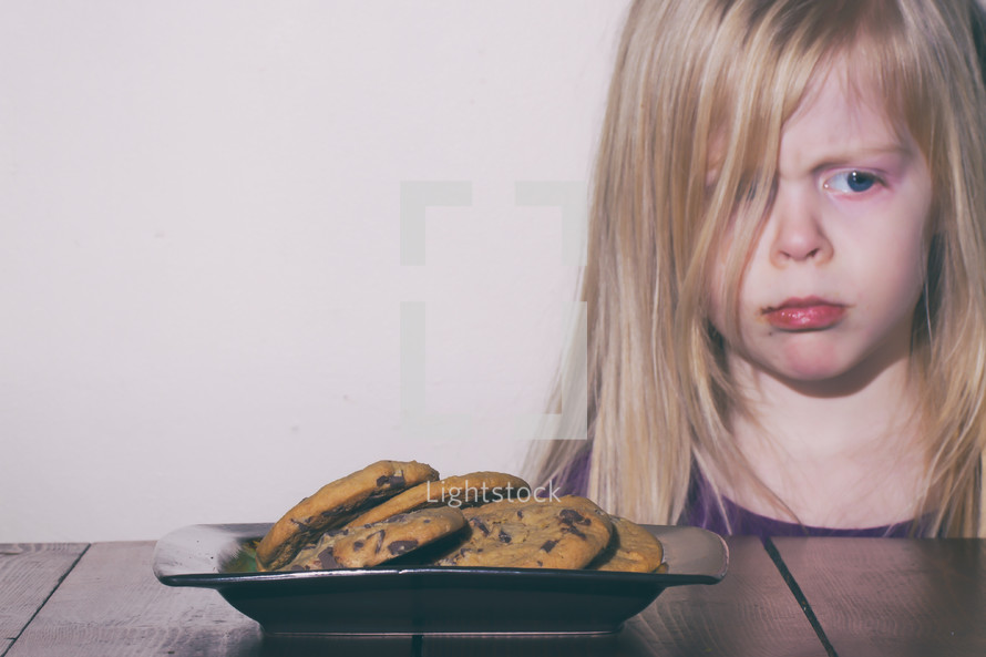 child frowning staring at cookies