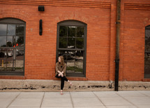 woman sitting near a red brick warehouse building