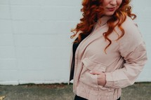 a redhead woman with her hands in her pockets