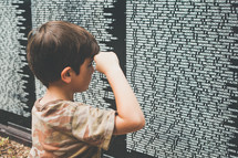 a child showing respect  at the Vietnam veterans memorial wall