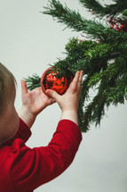 toddler playing with a Christmas ornament on a tree
