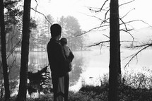 a father holding his baby and view of a lake