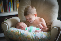 a big brother holding his baby brother